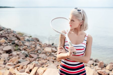 elegant girl in retro striped swimsuit posing with tennis racket on rocky beach