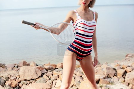 cropped view of sportswoman in retro striped swimsuit posing with white tennis racket on rocky beach near sea
