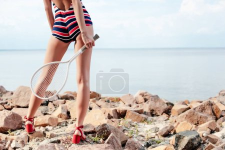 cropped view of young woman in striped swimwear holding tennis racket on rocky beach