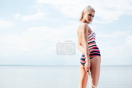 attractive blonde sportswoman in striped swimsuit holding tennis racket near sea with sky