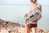 cropped view on girl in striped swimsuit posing with vintage boombox on rocky beach