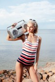 beautiful blonde woman in vintage swimsuit posing with cassette recorder