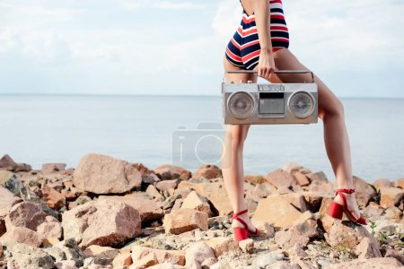 cropped view of woman in swimsuit holding vintage boombox on rocks near the sea