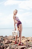 fashionable girl in striped swimsuit posing with vintage boombox on rocky beach