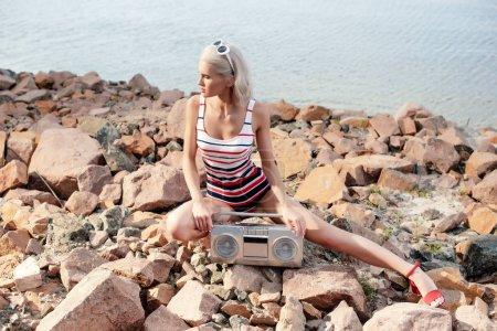 Foto de Atractiva mujer rubia en traje de baño sentado en la orilla rocosa con boombox vintage - Imagen libre de derechos