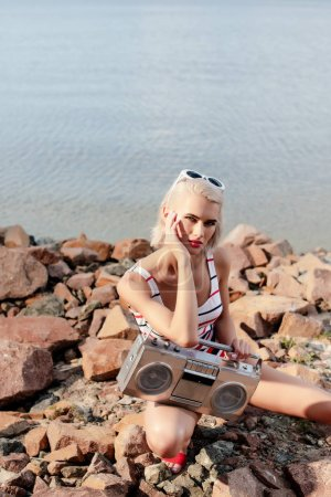 beautiful blonde woman in swimsuit posing with vintage boombox on rocky beach