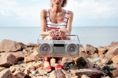 cropped view of girl posing with vintage boombox on rocky shore