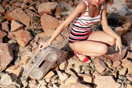 Foto de Recortada visión de mujer elegante en traje de baño rayado con boombox vintage en rocas - Imagen libre de derechos