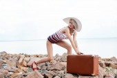 attractive stylish tourist in swimsuit posing with retro travel bag on rocky beach