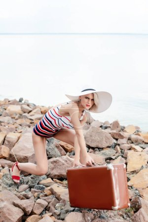 stylish tourist in swimsuit with vintage travel bag on rocky beach