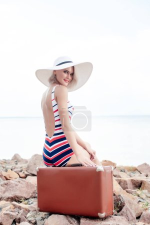 female tourist in swimsuit and white hat sitting on vintage travel bag on rocky beach