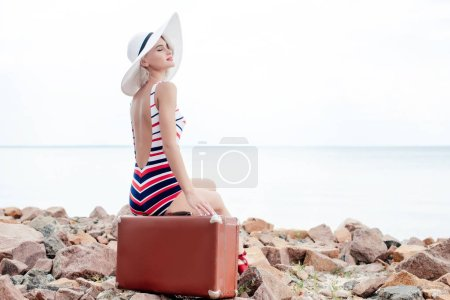 beautiful woman in striped swimsuit and hat sitting on retro travel bag on rocky beach
