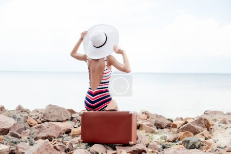 back view of fashionable tourist in striped swimsuit and hat sitting on retro travel bag on rocky beach