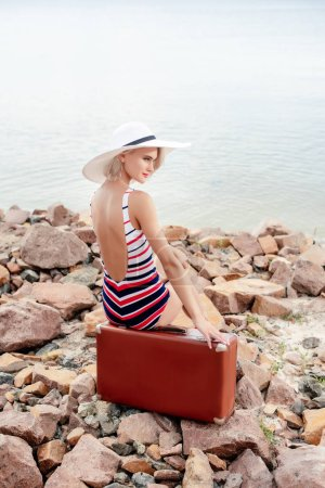 Photo for Attractive girl in vintage swimsuit sitting on travel bag on rocky beach - Royalty Free Image