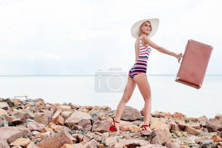 stylish elegant woman in swimsuit holding vintage suitcase on rocky shore