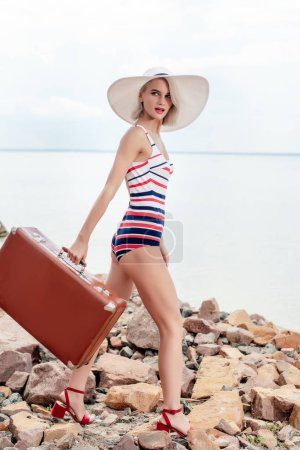 stylish womna in striped swimsuit and hat with vintage suitcase on rocky beach