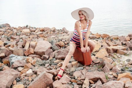 beautiful female tourist in swimsuit sitting on vintage travel bag on rocky beach