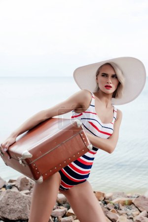 stylish tourist in swimsuit with vintage travel bag near the sea
