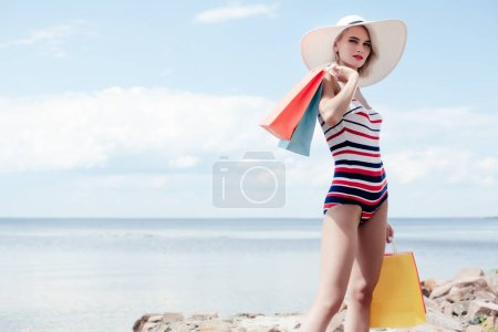 beautiful model in vintage striped swimsuit and white hat posing with shopping bags