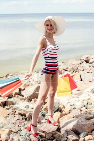 beautiful blonde woman in retro striped swimsuit holding shopping bags on rocky beach