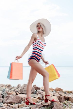 girl in striped swimsuit and white hat holding shopping bags on rocky beach