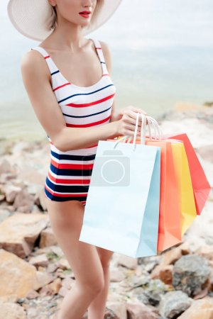 cropped view of woman in retro striped swimsuit holding shopping bags