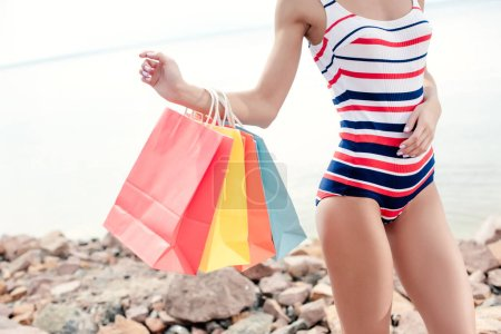 cropped view of girl in retro striped swimwear holding colorful shopping bags