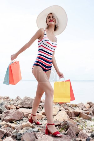 attractive woman in striped swimsuit and white hat posing with shopping bags