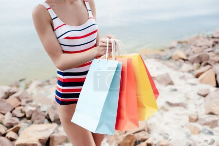 partial view of girl in retro striped swimwear holding colorful shopping bags on shore
