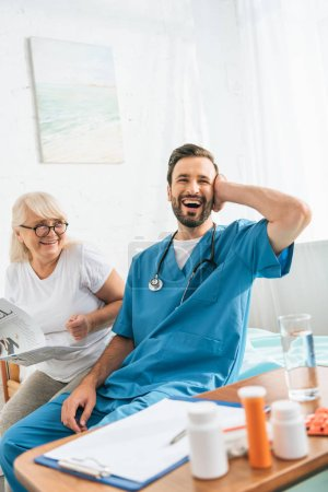 happy senior woman in eyeglasses holding newspaper and looking at cheerful young doctor laughing while sitting on hospital bed