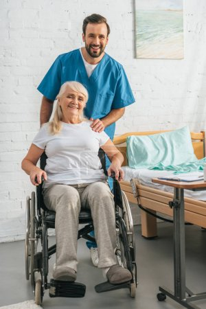 cheerful young male nurse and happy senior woman in wheelchair smiling at camera