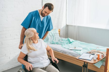 high angle view of smiling male nurse looking at senior woman in wheelchair