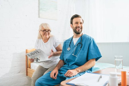 smiling young doctor with stethoscope sitting on hospital bed with happy senior woman reading travel newspaper
