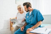 young doctor with stethoscope looking at senior woman reading travel newspaper in nursing home