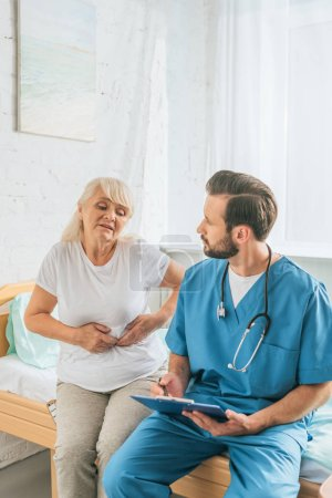 young doctor writing on clipboard and looking at sick senior woman sitting on hospital bed