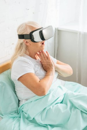 high angle view of shocked senior woman using virtual reality headset in hospital bed