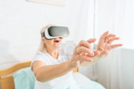 close-up view of smiling senior woman using virtual reality headset in hospital bed
