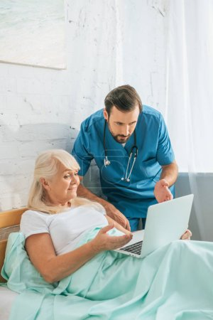 young doctor with stethoscope looking at senior woman using laptop in hospital bed