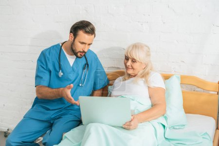 male nurse with stethoscope looking at senior woman using laptop in hospital bed