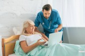 doctor with stethoscope looking at senior woman using laptop in hospital bed