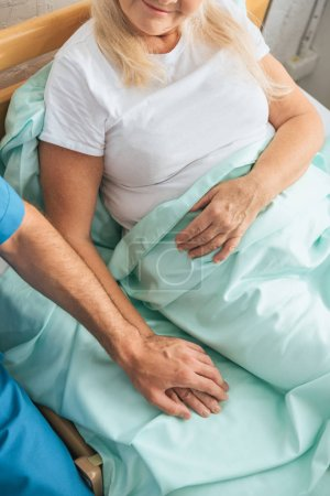 partial view of male nurse holding hand of sick senior woman lying in hospital bed