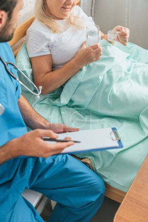 cropped shot of doctor writing on clipboard while senior woman taking medicine in bed