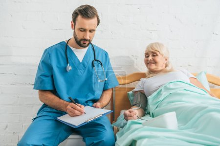 male nurse writing on clipboard while measuring blood pressure to smiling senior woman lying in bed