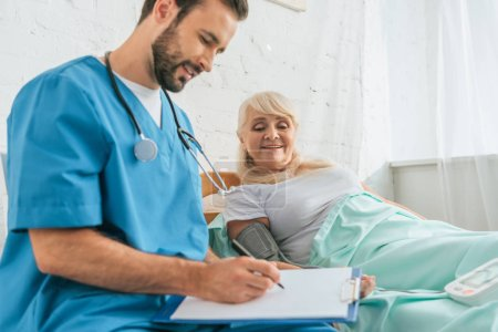 smiling male nurse writing on clipboard while measuring blood pressure to senior woman lying in bed