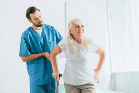 male nurse supporting senior woman with walking cane