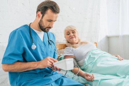Photo pour Jeune infirmier avec stéthoscope tenant un tensiomètre tout en mesurant la pression artérielle chez une femme âgée couchée au lit - image libre de droit