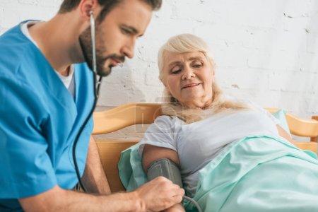 Photo pour Jeune infirmière masculine mesurant la pression artérielle chez une femme âgée dans un lit d'hôpital - image libre de droit