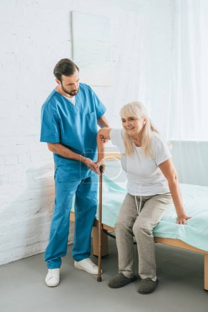 male nurse helping senior woman with walking stick