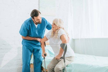 Photo pour Travailleur social masculin aidant femme âgée malade avec des béquilles - image libre de droit