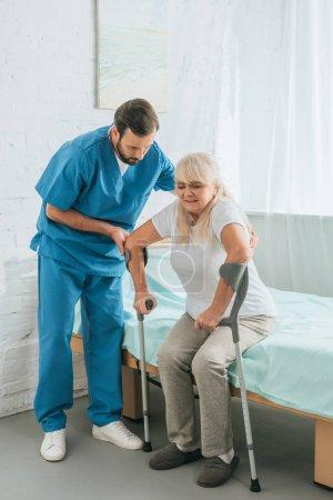 enfermera masculina ayudando a una mujer mayor con muletas sentada en la cama del hospital